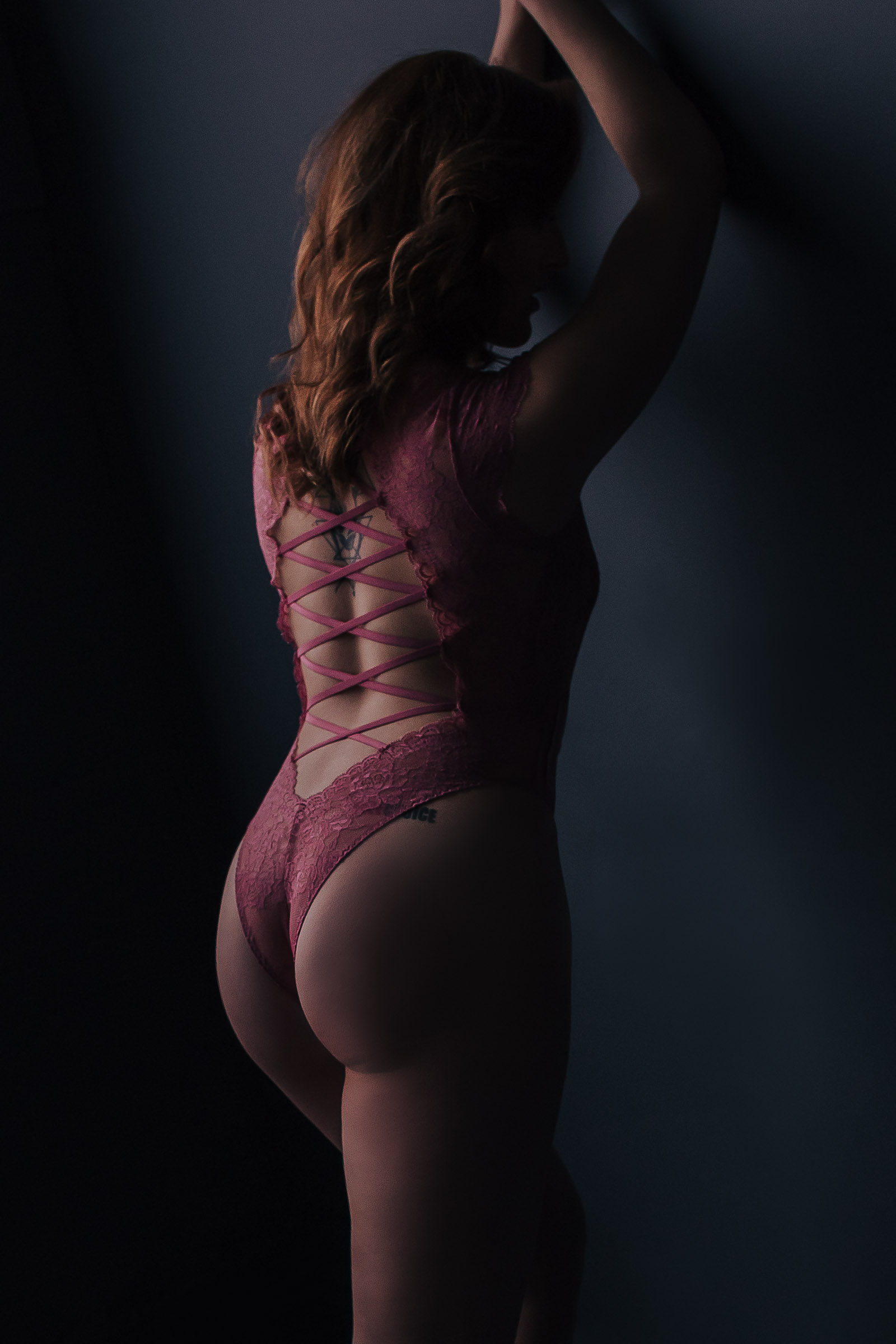Woman wearing pink bodysuit with strappy back for Toronto Boudoir Photography Session