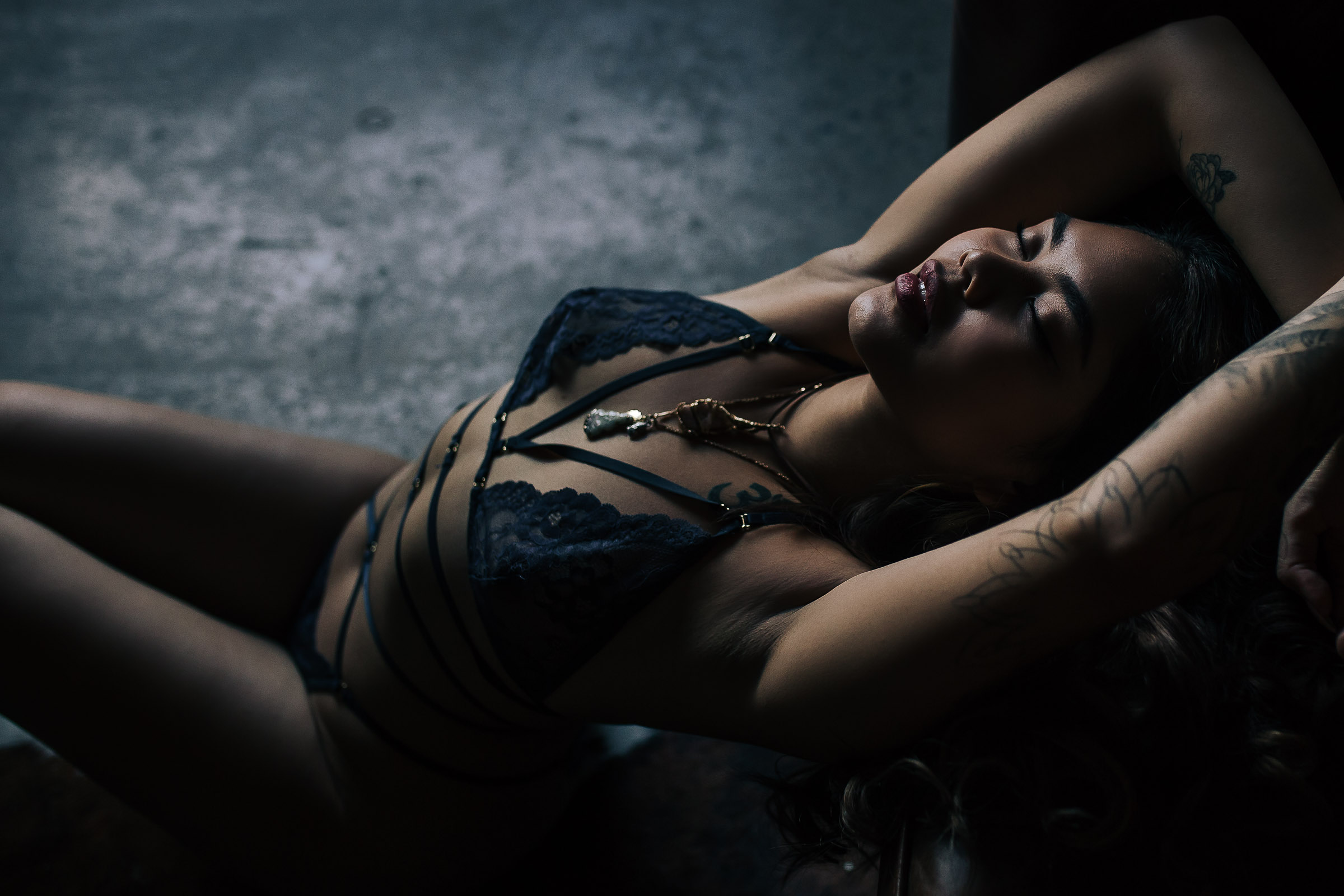 Beautiful Asian woman wearing strappy dark blue lingerie for Toronto boudoir photography session