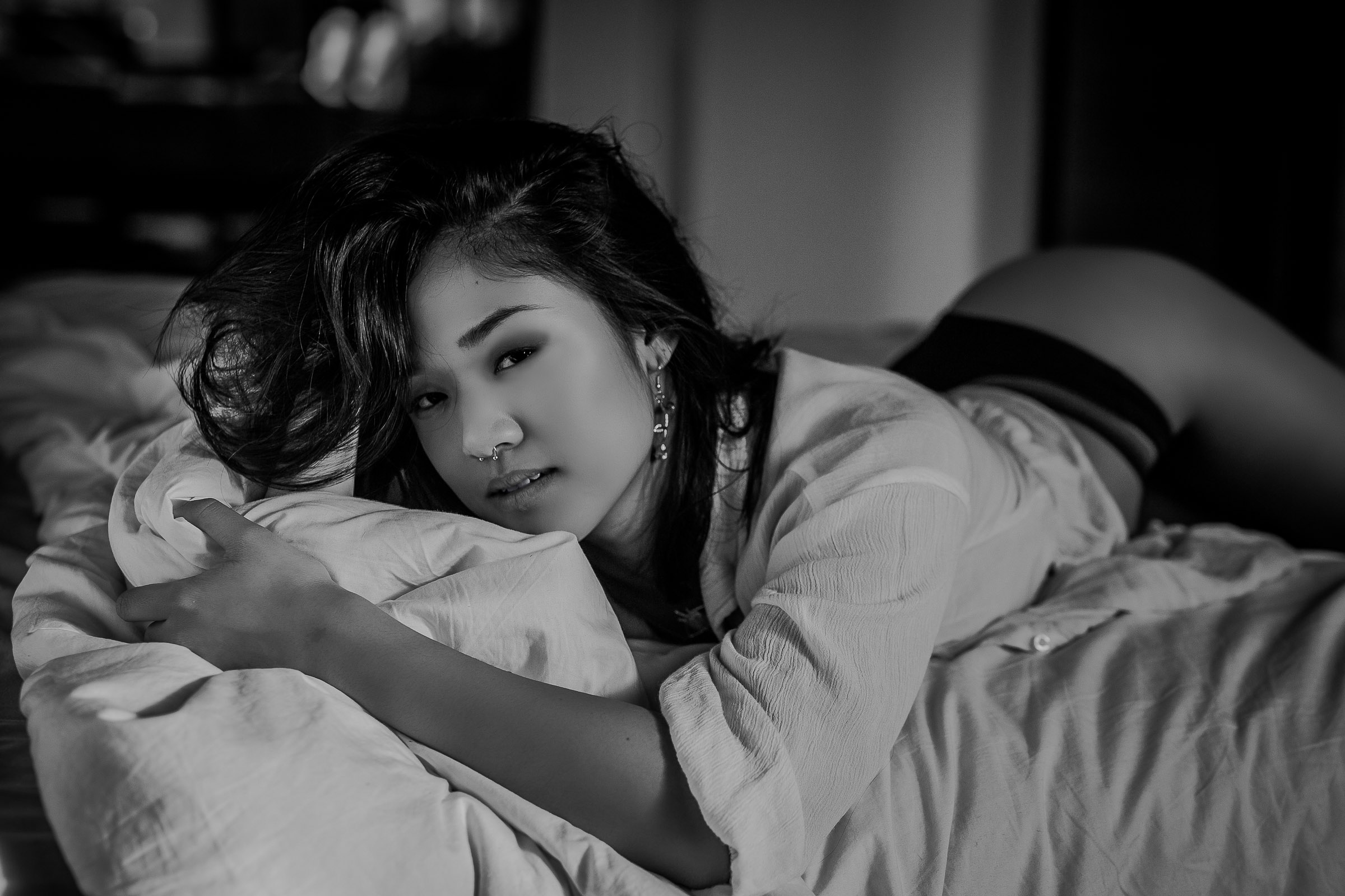 Beautiful Asian woman lounging on bed wearing white shirt in Toronto boudoir studio