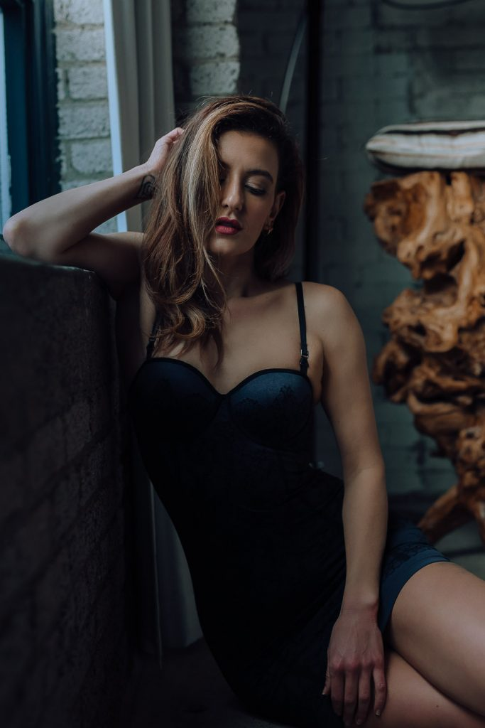Beauty boudoir portrait of woman wearing black lingerie slip dress