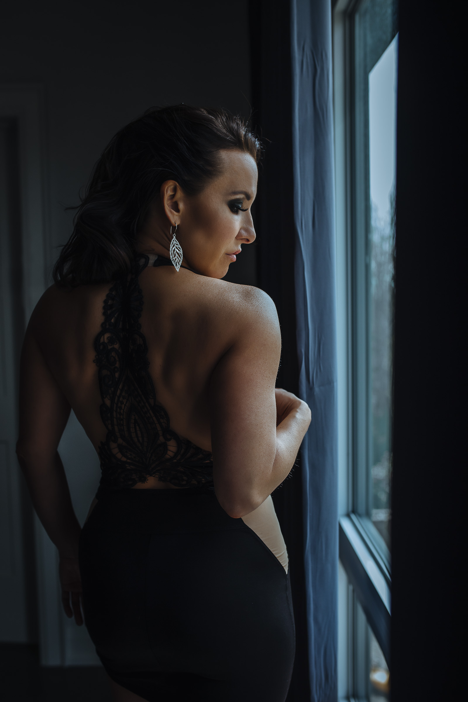 Woman standing at window of Toronto boudoir studio