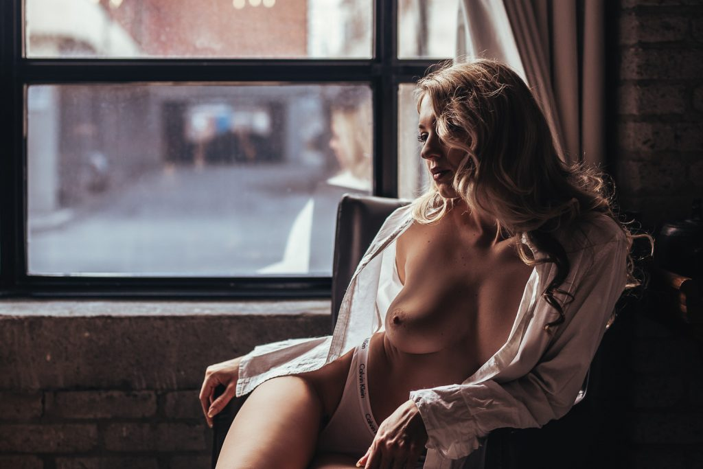 Blonde woman wearing white dress shirt for Toronto boudoir photography session